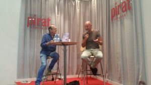 Petter Lidbeck intervjuas av Fredrik Belfrage i Piratförlagets monter.