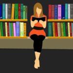 Kvinna som sitter och läser en bok framför en vägg med bokhyllor